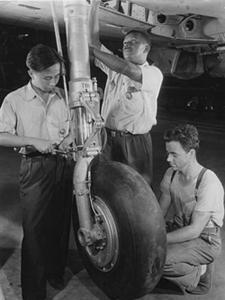 3 men working on plane wheel
